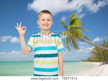 childhood, gesture, summer, travel and people concept - smiling little boy making ok sign over tropical beach background
