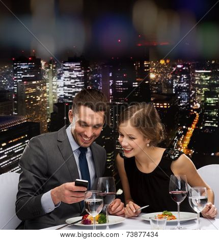restaurant, technology, couple and holiday concept - smiling couple taking picture of main course with smartphone camera at restaurant