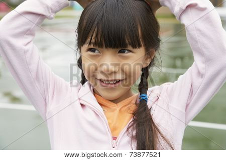 Asian girl with hands on head