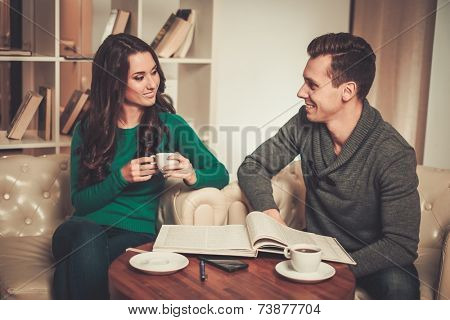 Couple with coffee and book discussing something in cafe