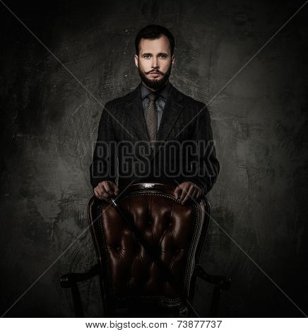 Handsome well-dressed man with walking stick standing near leather chair