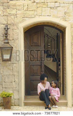 African mother and daughter sitting on doorstep