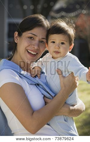 Hispanic mother holding baby outdoors