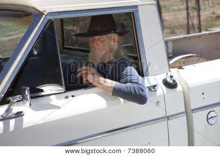Senior Man With Cowboy Hat Sitting In Vehicle