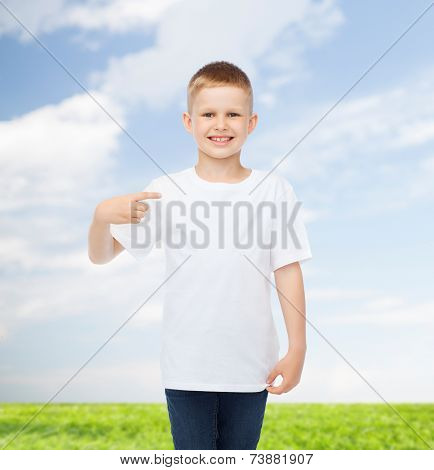advertising, people and childhood concept - smiling little boy in white blank t-shirt pointing finger at himself over natural background