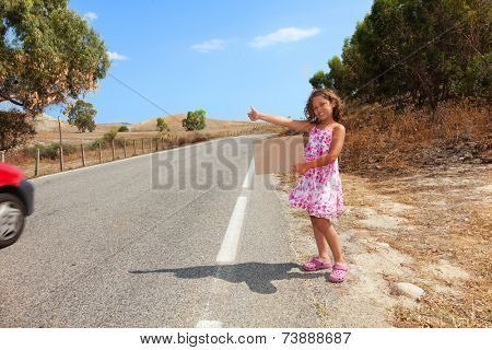 young girl hitchhiking along the street