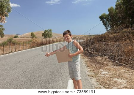 young boy hitchhiking along the street