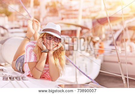 Happy blond female lying down on sailboat and enjoying beautiful sunset, summer adventure on luxury water transport, pleasure and relaxation concept