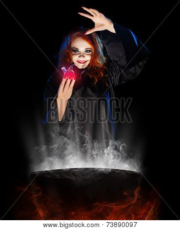 Young witch with red potion and cauldron  isolated