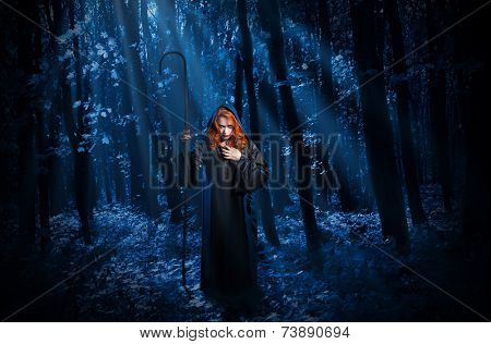Young witch with staff in night forest
