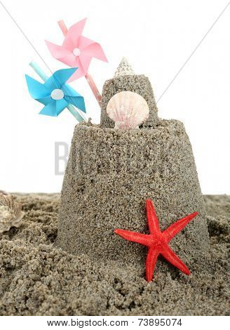 Sandcastle with pinwheel on sandy beach, isolated on white