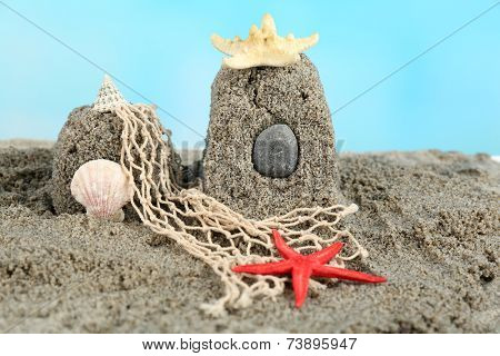 Sandcastle with starfish on sandy beach