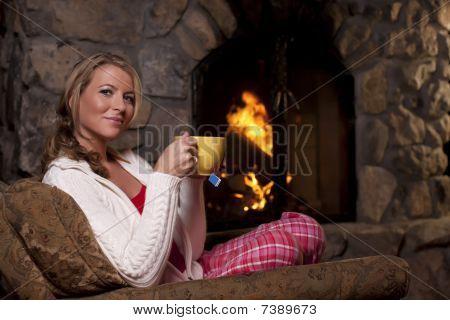Mulher com chá sentado perto da lareira