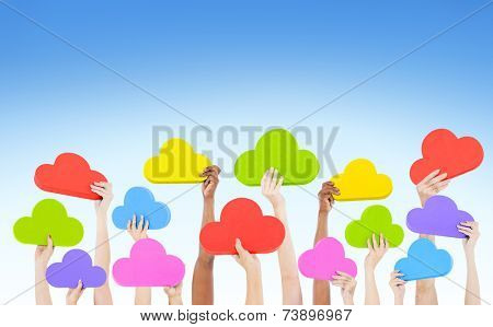 Hands holding multi colored cloud shaped speech bubbles with blue sky.