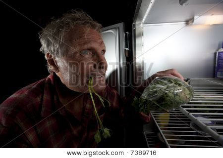 Eccentric Man Staring Into Refrigerator With Greens In His Mouth