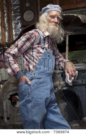 Senior Mechanic Posing By Car