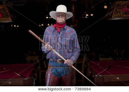 Senior Cowboy Standing In A Pool Hall