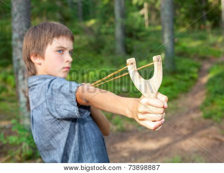 Boy aiming wooden slingshot outdoors