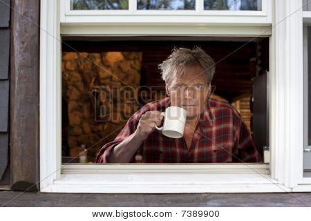 Mann mit Kaffeetasse Blick aus Fenster