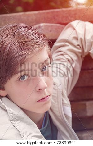 Toned Image Of A Cool Teenage Boy Leaning On A Stack Of Flagstones
