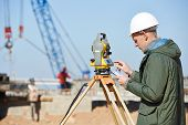 image of theodolite  - Surveyor builder worker with theodolite transit equipment at construction site outdoors during surveying work - JPG