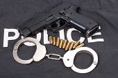stock photo of snitch  - security concept with gun ammo and handcuffs - JPG