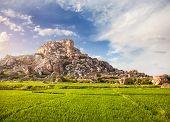 stock photo of karnataka  - Rice plantation near Hanuman monkey temple on the big stone hill at blue sky in Hampi Karnataka India - JPG