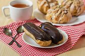 stock photo of eclairs  - Tasty eclairs on table with tea cup - JPG