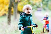 picture of four-wheel drive  - Two little siblings boys having fun on bikes in autumn forest - JPG
