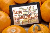 image of pumpkin pie  - Happy Thanksgiving word cloud on a digital tablet surrounded by pumpkins - JPG