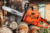 stock photo of chainsaw  - The orange chainsaw lying on firewood outdoors - JPG