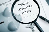 picture of insurance-policy  - Magnifying glass over health insurance policy and piggy bank - JPG