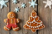 stock photo of gingerbread man  - Christmas homemade gingerbread man and tree on wooden table - JPG