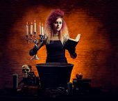 stock photo of dungeon  - Young and beautiful witch making a witchcraft in dungeon - JPG