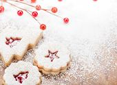 foto of linzer  - Christmas Linzer cookies decorated with powdered icing sugar and red decorations in the background - JPG