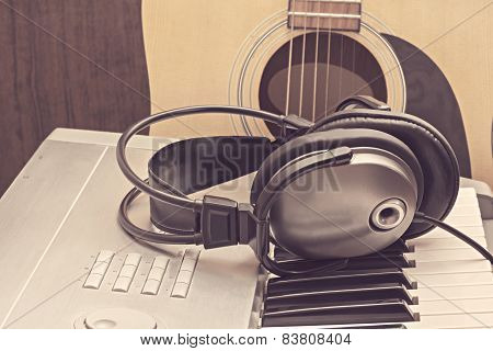 Digital Midi Keyboard, Headphones And Acoustic Guitar.