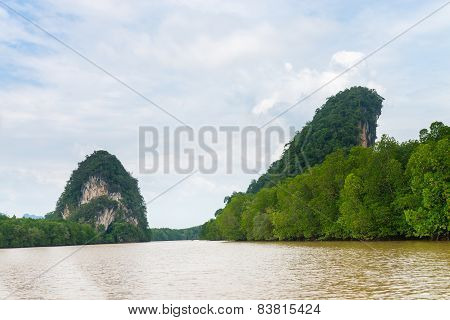 Two Limestone Cliffs Above Tropical River And Mangrove