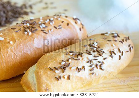 A pair of bread rolls on wooden table