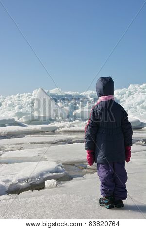 Little Cute Girl And Hummock On The Frozen Sea Shore