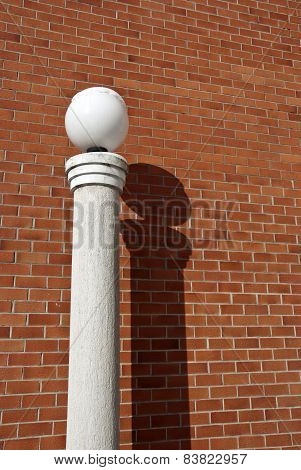 Modern Lamp On Column Near Red Brick Wall