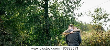 Young Couple Hugging In A Forest