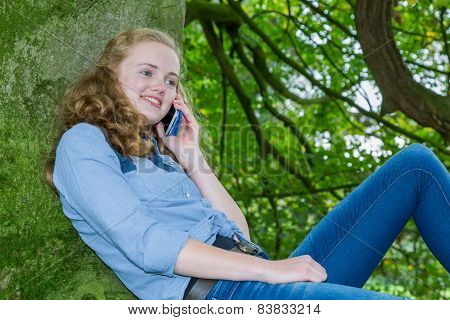 Teenage girl phoning mobile in geen tree