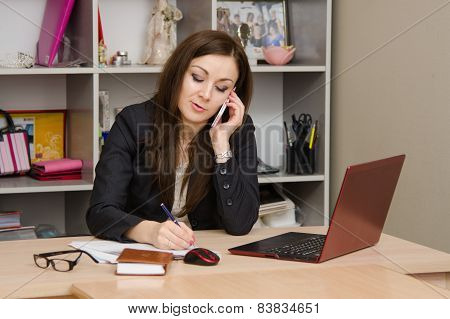 Business Woman In Office Talking On Phone And Writes Table