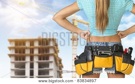 Woman in tool belt standing backwards, akimbo. Cropped image. Building under construction as backdro