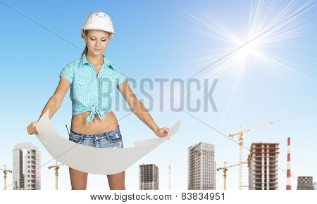 Woman in helmet holding paper sheet. Looks at paper. Construction site as backdrop