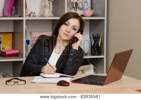 Office Girl Writes In Notebook On Information Obtained From A Telephone Conversation