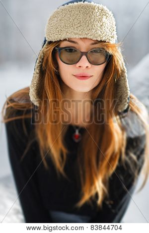 Portrait of a beautiful young woman in a earflap-hat