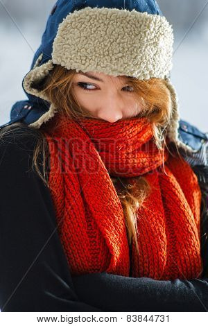 Portrait of a beautiful young woman wearing a red scarf and earflap hat