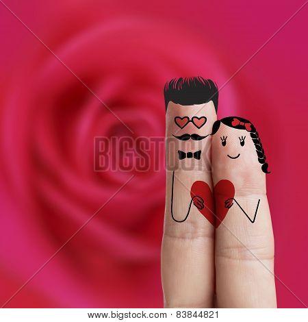 Conceptual finger art. Lovers is embracing and holding red heart. Stock Image