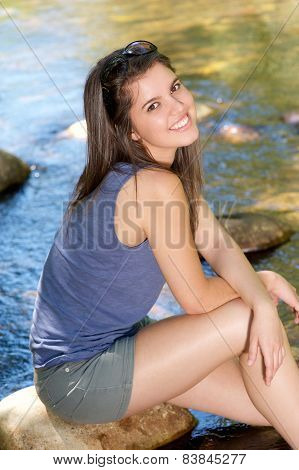 Happy Girl Sitting Next To Stream With Feet In Water